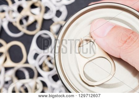Woman hand holding ring pull cans opener on black metallic background