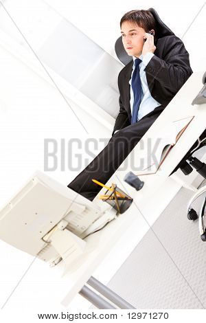 Young business man sitting in office with feet on desk and talking on mobile phone