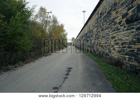 A driveway runs parallel and adjacent to the exterior wall on the side of the old Illinois State Penitentiary in Joliet, Illinois.