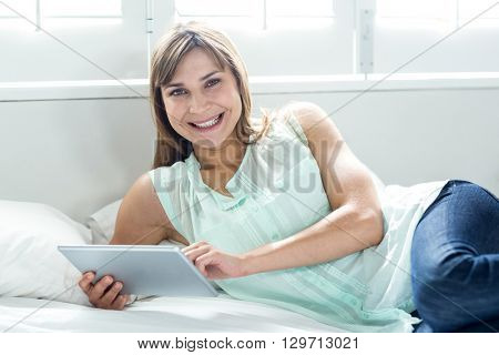 Portrait of beautiful woman smiling while using digital tablet on bed at home