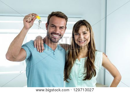 Portrait of happy couple with key at new house
