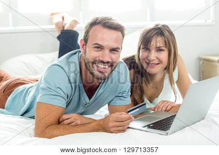 Portrait of happy couple online shopping while relaxing on bed at home