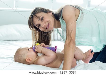 Happy woman with playful son on bed at home