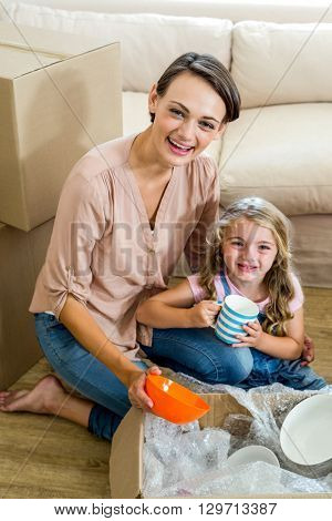 Portrait of mother and daughter unpacking box in new house