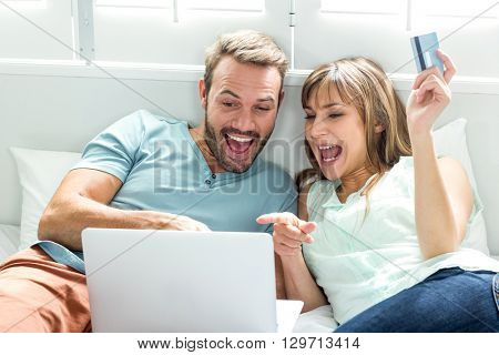 Couple screaming while looking in laptop on bed at home