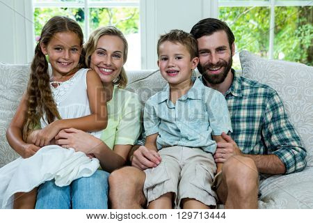 Portrait of happy children with parents sitting on sofa
