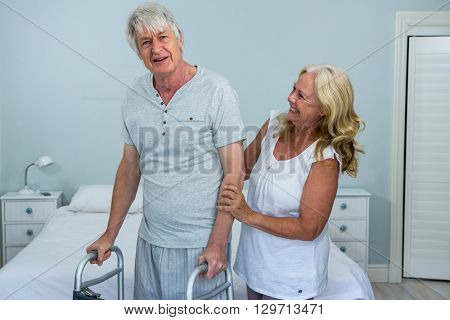 Happy senior woman helping man to walk in bedroom at home