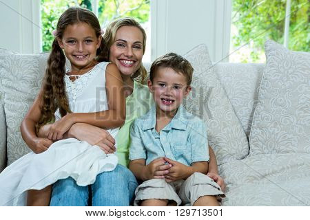 Portrait of cheerful mother with daughter and son on sofa at home