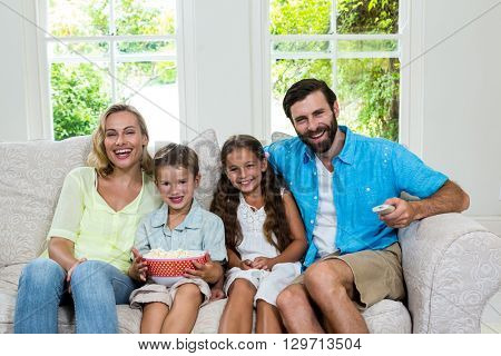 Portrait of happy family laughing while watching tv at home