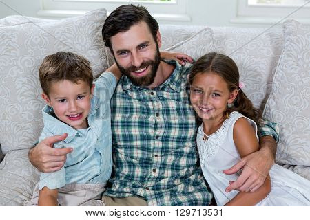 Portrait of happy father with children on sofa at home