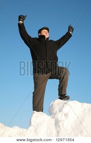 elderly man on snow hill with hand up