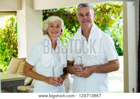 Portrait of happy active senior couple holding water bottles