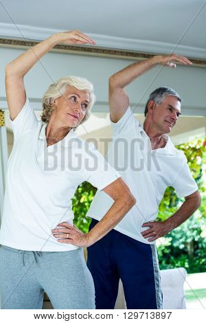 Senior couple bending while doing aerobics at home