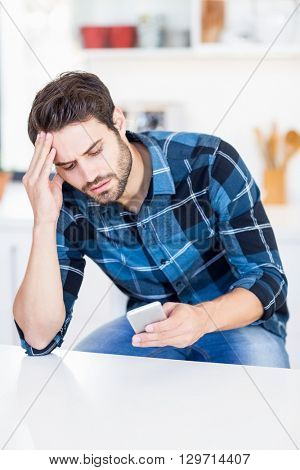 Worried man text messaging on mobile phone in the kitchen