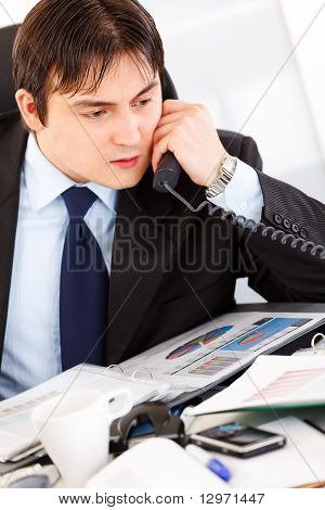 Concentrated modern businessman sitting at office desk and talking on phone