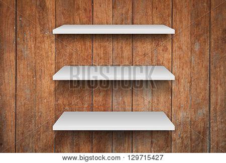 Three white shelves on wooden interior texture background, stock photo