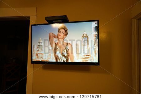HARBOR SPRINGS, MICHIGAN / UNITED STATES - DECEMBER 23, 2015: Charlize Theron appears on a commercial advertisement on a flat-screen television attached to a wall in a Harbor Springs home.