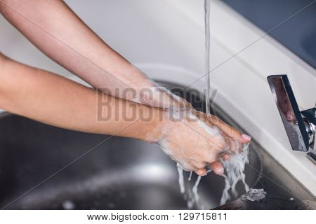 Cropped image of woman rinsing hands in washbasin at home