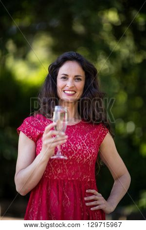 Portrait of smiling young woman holding champagne flute