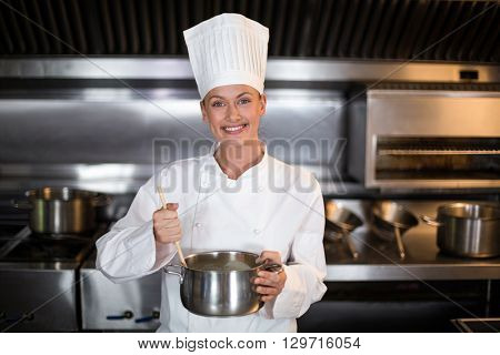 Portrait of happy female chef holding saucepan in commercial kitchen