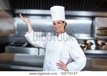 Portrait of happy female chef gesturing while standing in commercial kitchen