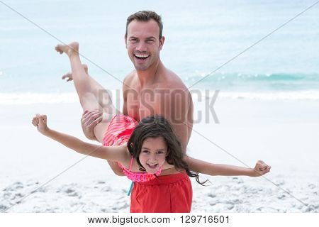 Happy father carrying daughter while standing at beach