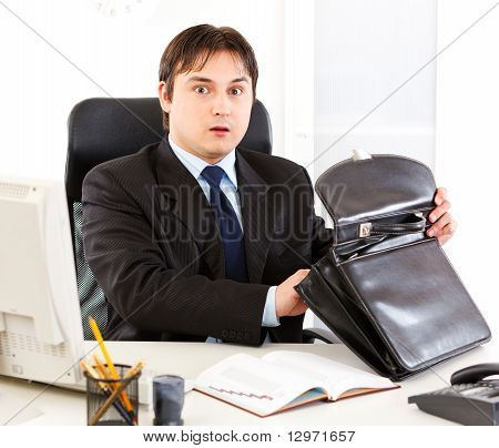 Shocked businessman sitting at office desk and holding open suitcase in hands