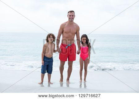Full length of father and children standing on sea shore at beach