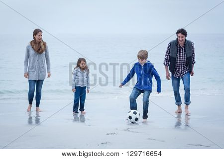 Happy family playing soccer at sea shore
