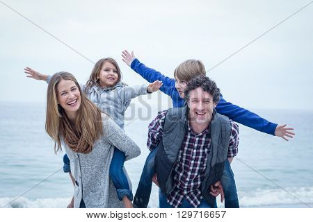 Happy parents carrying children and enjoying at sea shore