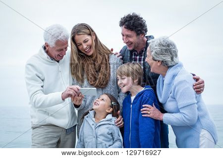 Happy family looking in phone at beach against sky