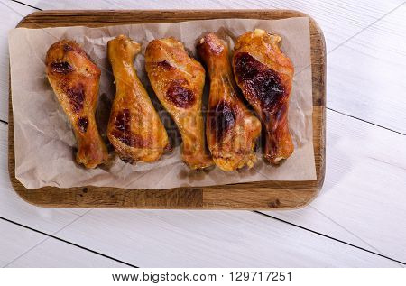 Roasted chicken legs on a wooden board top view