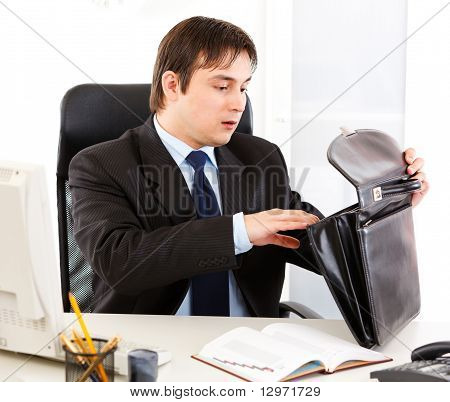 Shocked modern businessman sitting at office desk and searching something in briefcase