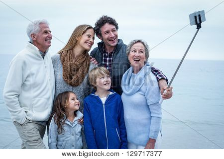 Happy family taking selfie at beach against sky
