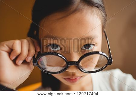Schoolchild holding her glasses at school