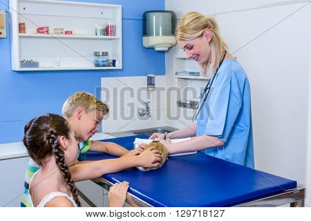 A woman vet taking notes while children petting a rabbit on the operating table