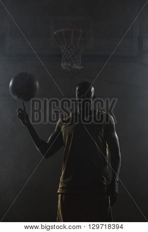 Basketball player turning the ball on his finger on a gym