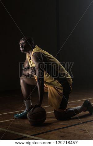 Portrait of basketball player with a knee on the floor and a hand on the ball looking up on a gym