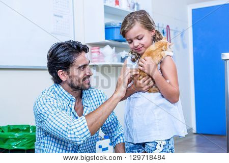 A little girl bringing a kitten with her father at medical office