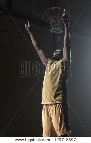 Portrait of basketball player throwing arms for the victory on a gym