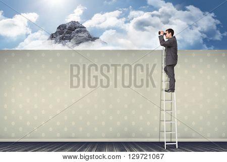 Businessman standing on ladder using binoculars against room with wooden floor