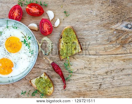 Country breakfast set with fried egg and cherry-tomatoes on a wooden desk