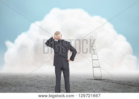 Rear view of doubtful mature businessman against giant white cloud above desert