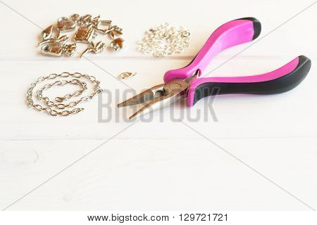 Pliers, chain, metal rings and pendants on a white wooden background. How to make yourself metal bracelet