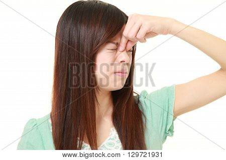 portrait of young woman suffers from Asthenopia on white background