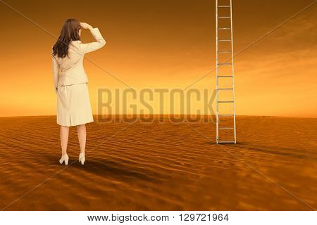 Rear view of young businesswoman looking away against desert scene