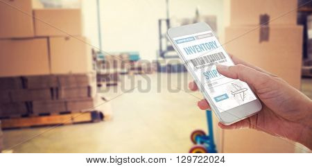 Cropped hand using smartphone against boxes on trolley in warehouse