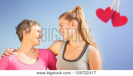 Composite image of mother and daughter looking each other with a blue background