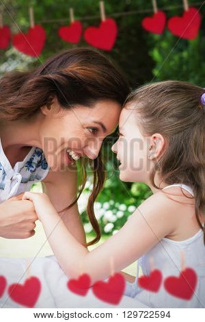 Composite image of mother and daughter looking each other behind heart tinsel
