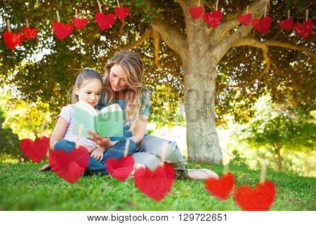 Mother and daughter reading a book at park against hearts hanging on a line
